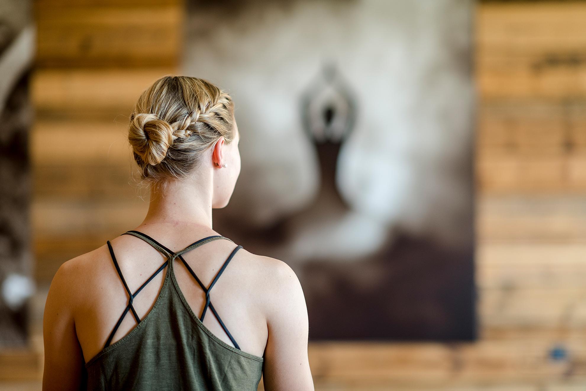 Dame mit Dutt im Yoga-Raum betrachtet Bild im Hotel DAS.GOLDBERG nahe Gastein