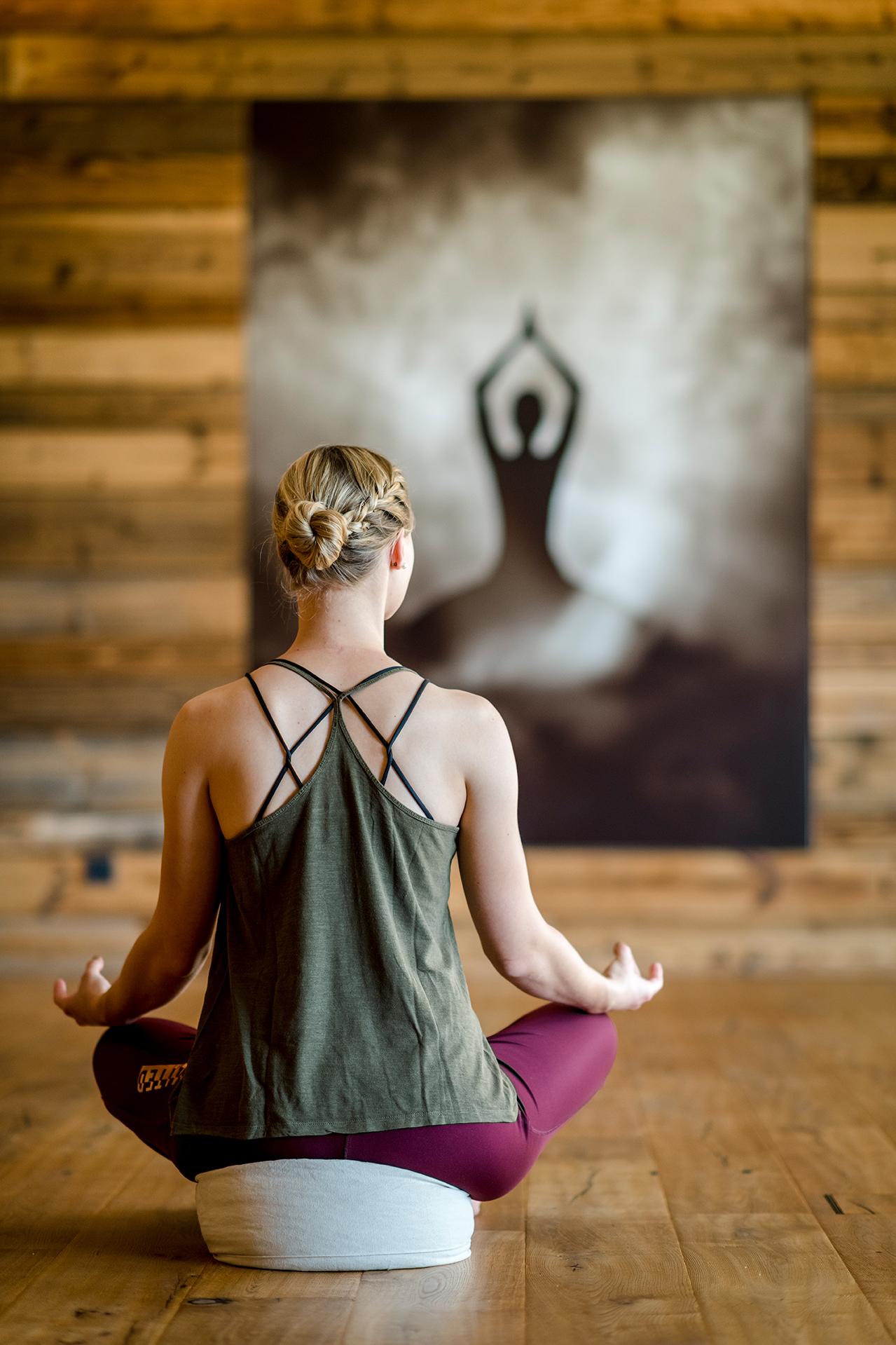 Dame in Sportbelkleidung sitzt in Yoga-Position mit dem Rücken zum Fotografen gewandt im Yoga-Raum des Hotels DAS.GOLDBERG bei Gastein
