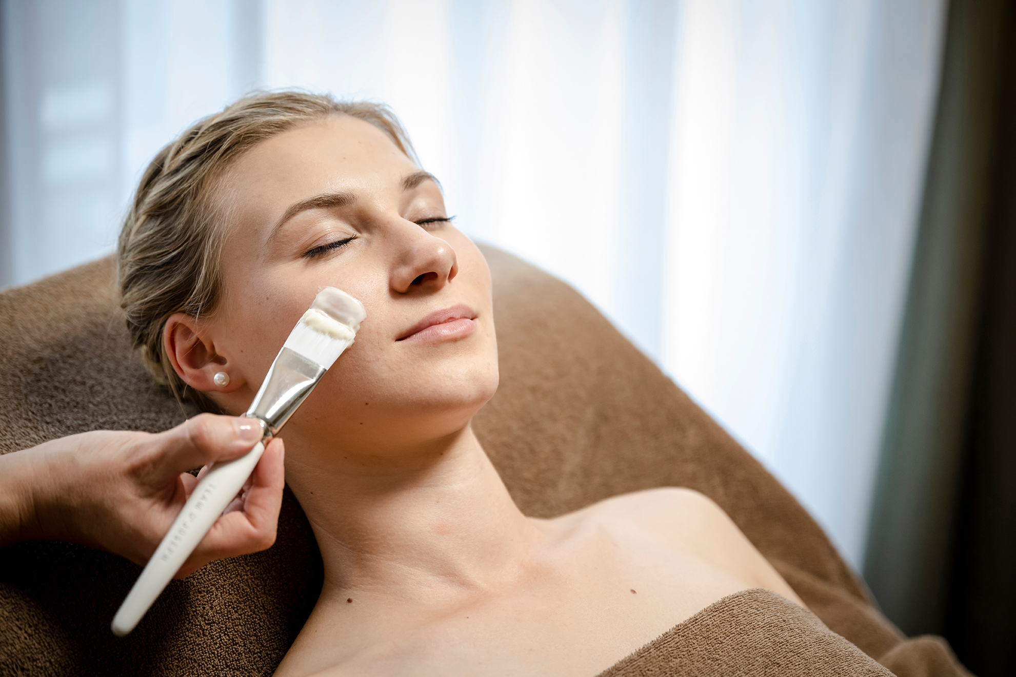 Dame mit geschlossenen Augen entspannt bei Beauty-Anwendungen im Hotel DAS.GOLDBERG nahe Salzburg
